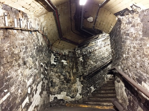 Fire damaged tunnels dating from the awful King's Cross fire of November 1987. These are still retained for maintenance purposes; you can see how the heat melted the adhesive holding the tiles to the wall. Note also the wooden handrails and indeed wooden steps.