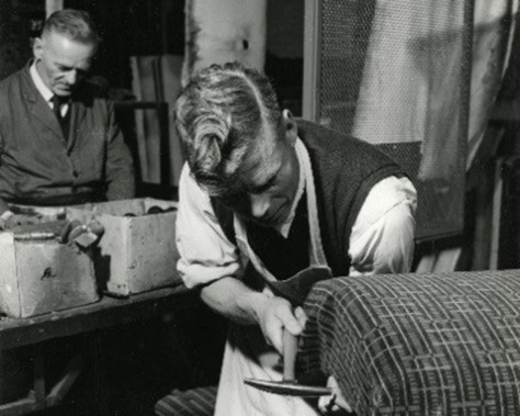 Men working in a shop. One is fitting a moquette.
