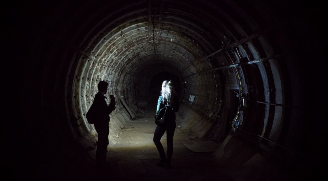 A man and a woman shining a light down an abandoned tunnel