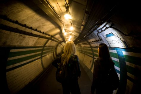 Two women look down a disused tunnel at Piccadilly Circus