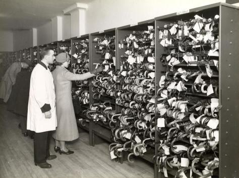A man and a woman look through a shelf full of umbrellas.