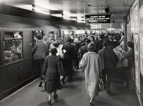 Black and white photo of people on a station's platform boarding a train