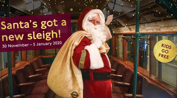Santa posing in a vintage Tube train with a sack on his shoulder.