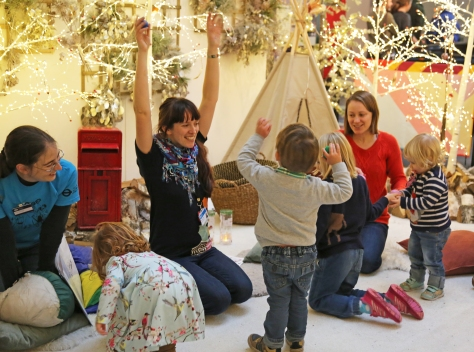 A group adults and children smiling and dancing in a mock up forest with Christmas lights and trees.