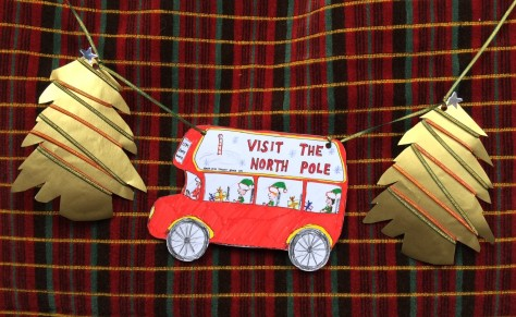 Christmas bunting with two gold pine trees and a red double decker bus with elves.