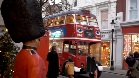 A man, woman and two children looking at at red double decker bus parked on a street with Christmas decorations.