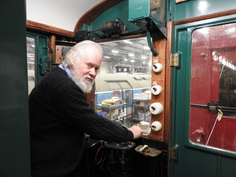 A man standing in the driving cab of a vintage train