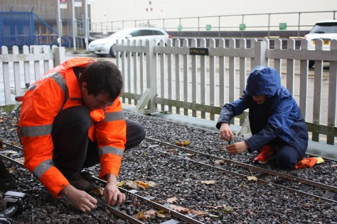 A child and an adult wearing a hi-vis jacket screw bolts into the tracks of a miniature rail.