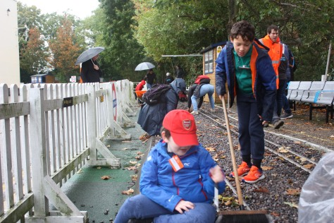 Children and adults sweeping leave off a miniature rail track