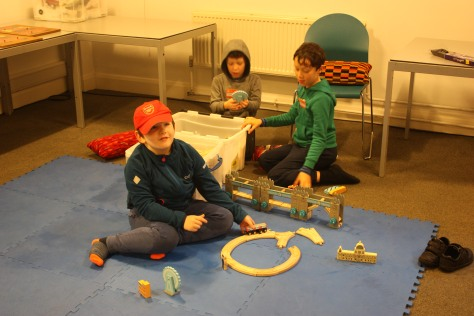 Three cildren play with a wooden train model while sitting on soft mats