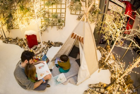 A dad and his two children read a book while sitting in a mock up forest with Christmas lights, trees and a tepee.