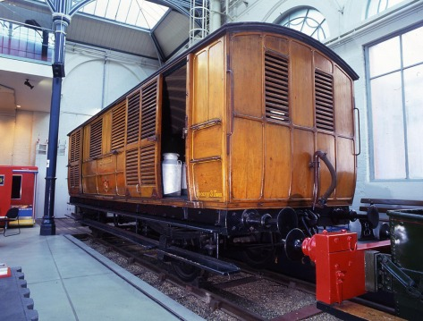 Colour photo of a brown wooden milk van. Tin milk containers are visible inside