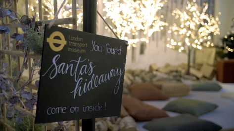 In the foreground, a sign reading 'You Found Santa's Hideaway. come on inside'. In the background a cosy seating area with Christmas lights and decorations.