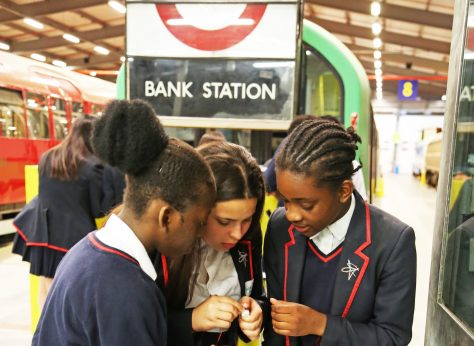 Three teenage girls look at an exhibit in the Museum depot