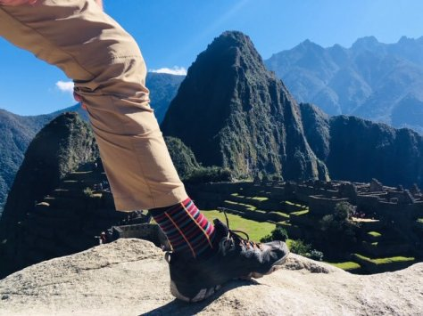 Close up of a leg with the mountain of Mavhu Picchu in the background
