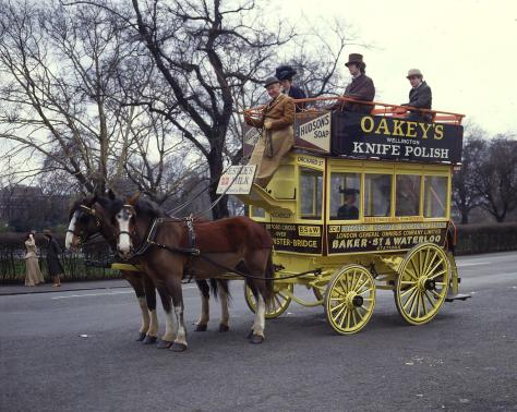 A yellow carriage with three passengers, being hauled by two brown and white horses