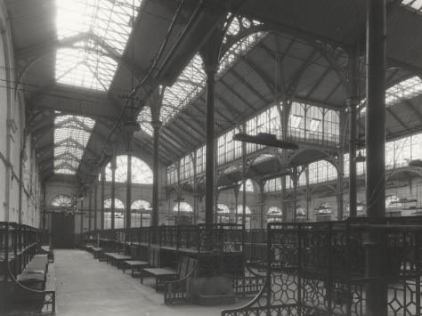 Black and white photo of an old building with high ceilings. metal framed windows ans market stalls