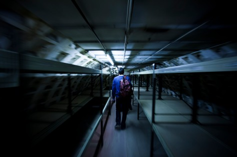 A an walks between rows of bunk beds in an underground shelter