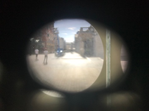 Picture from inside the Museum looking through the shutters out onto Covent Garden Piazza. Two people can be seen outside in the Piazza