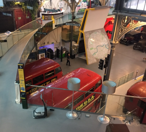 View from second floor looking down over buses inside London Transport Museum. Maintenance man walking across Museum floor