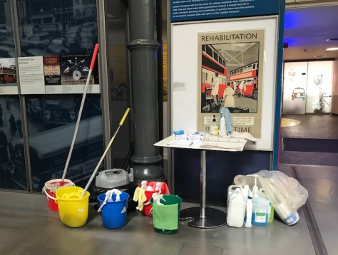 Cleaning products including two mops and buckets, a blue, red and green bucket sitting next to a table with cleaning rotas