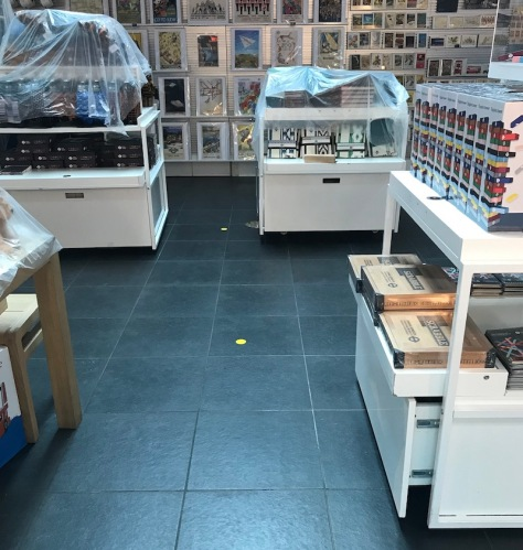 Inside London Transport Museum shop, with a focus on the clean floor tiles with four covered stands of shop products.