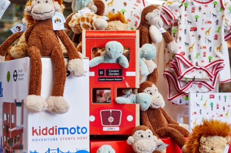 Monkey, giraffe, turtle and lion soft toys sitting in and next to a wooden red London bus and baby clothing