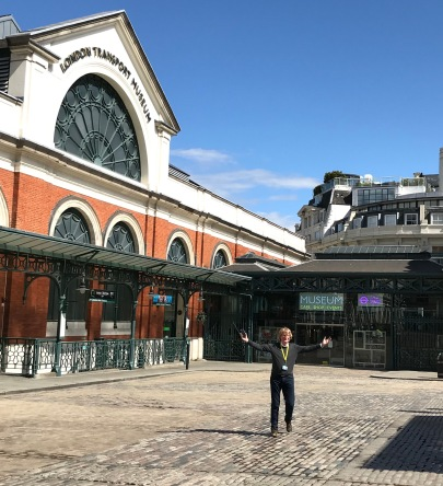 Sam Mullins standing with his arms out-wide in Covent Garden Piazza in front of London Transport Museum