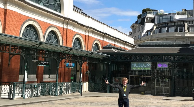 Director Sam Mullins with open arms stands in the middle of Covent Garden piazza with the Museum entrance in the background