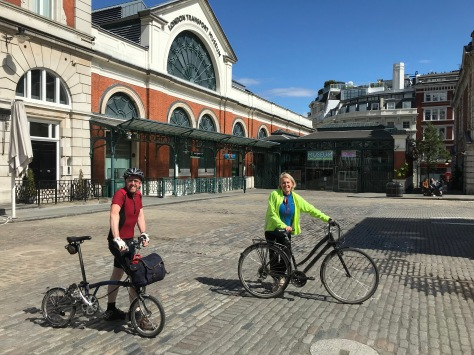 A man and a woman stand with their bikes in Covent Garden Piazza with London Transport Museum in the background