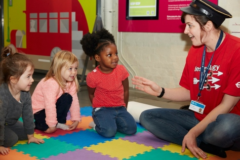Three young girls watching a member in our Learning team wearing a train conductors hat during a Singing and Stories session