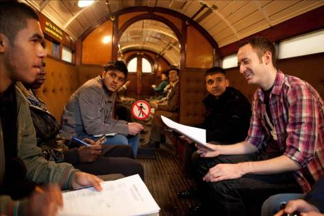 Five male pupils and a teacher talking inside a heritage train at London Transport Museum