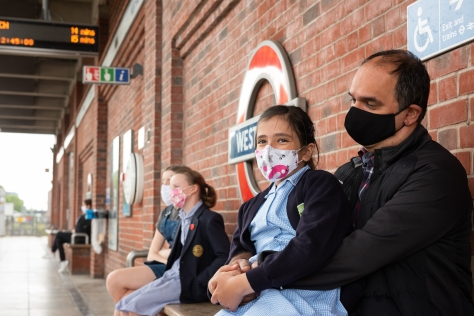 Daughter sitting on Father's lap at West Ham station platform and both are wearing facemasks