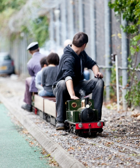 London Transport Museum Miniature Railway. Driver is facing away from camera with three passengers on board behind him