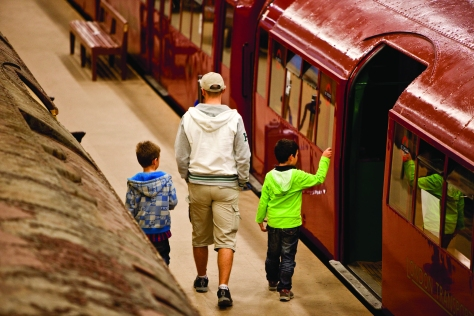 A man and two children walk by a red underground train