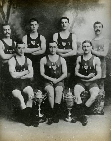Black and white photo of six men in swimming gear with two trophy cups in front of them
